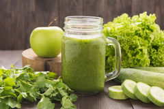 Healthy green vegetables and green fruit smoothie on rustic wood Royalty Free Stock Photo
