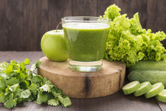 Healthy green vegetables and green fruit smoothie on rustic wood Stock Image