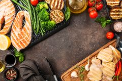 Healthy grill food. Healthy food - grilled salmon steak, chicken and vegetables over dark background, top view Stock Photo