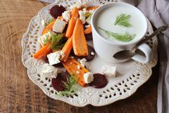 Healthy grilled beet, carrots salad with cheese feta, fennel and Greek yogurt in small glass bowls on the rustic wooden table, top stock images