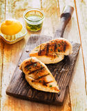 Healthy grilled chicken breasts. Marinated with lemon and olive oil and cooked on a summer BBQ served on an old wooden board Stock Photo
