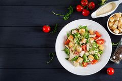Healthy grilled chicken Caesar salad with tomatoes, cheese and croutons. North American cuisine. Top view stock photos