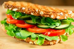 Healthy grilled vegan sandwich made of sprouted organic bread, tomato, cucumber, spinach and arugula. Selective focus Royalty Free Stock Photo