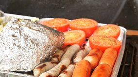 Healthy grilling in aluminum case. Cooking of white pepper, garlic, tomatoes , champignons, sausages  and potatoes. Wrapped in aluminum foil. The barbecue with stock video footage