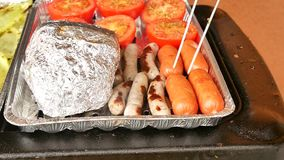 Healthy grilling in aluminum case. Cooking of white pepper, garlic, tomatoes , champignons, sausages  and potatoes. Wrapped in aluminum foil. The barbecue with stock footage