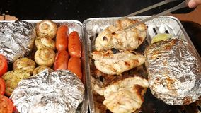 Healthy grilling in aluminum case. Cooking of white pepper, garlic, tomatoes , champignons, sausages  and potatoes. Wrapped in aluminum foil. The barbecue with stock video