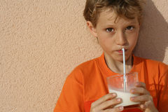 Healthy habits. Young boy sucking milk through a straw Royalty Free Stock Image