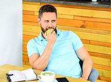 Healthy habits. Coffee break to relax. Healthy man care vitamin nutrition during working day. Physical and mental. Wellbeing concept. Man sit eat green apple royalty free stock photos