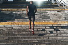 Healthy habits. Full length rear view of young African man in sports clothing running up the stairs while exercising outdoors royalty free stock photos