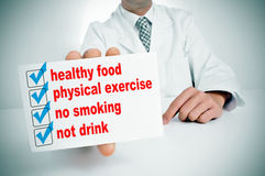 Healthy habits. A man wearing a white coat sitting in a desk showing a signboard with some healthy habits, such as healthy food, physical exercise or no smoking Royalty Free Stock Photo
