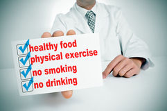 Healthy habits. A man wearing a white coat sitting in a desk showing a signboard with some healthy habits, such as healthy food, physical exercise or no smoking Stock Photo