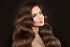 Healthy Hair. Beautiful model girl with shiny brown wavy long ha. Irstyle and makeup isolated on black background. Glossy natural hair. Care and hair products Royalty Free Stock Photo