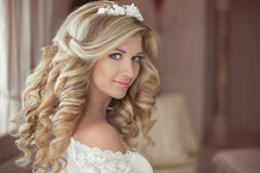 Healthy hair. Beautiful smiling girl bride with long blonde curl. Y hairstyle and bridal makeup. Wedding indoor portrait Stock Photo