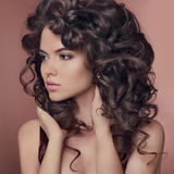 Healthy hair. Curly Hairstyle. Brunette girl model. Beautiful yo Stock Photos
