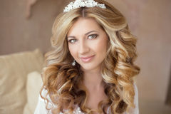 Healthy hair. Wedding makeup. Beautiful smiling girl bride with. Long blonde curly hairstyle.  bridal  indoor portrait Royalty Free Stock Image