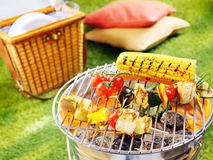 Healthy halloumi kebabs grilling over a fire. In a portable barbecue with tomatoes and fresh corn on the cob on a summer picnic in the garden Stock Images