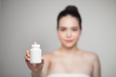 Healthy happy asian woman with pills bottle in hand. Royalty Free Stock Images
