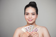 Healthy happy asian woman with pills in hand. Stock Photos
