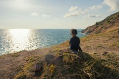 Young boy at cliff look seacape at sunset. Healthy happy boy with sunglasses sit on rock at cliff to see sunset and seascape after reaching to mountain summit by Stock Image