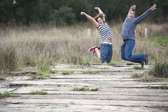 Happy couple jumping outdoors stock image