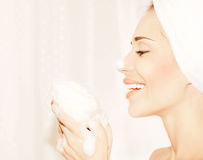 Healthy happy girl taking bath. Profile portrait of a beautiful young female cleaning face skin, hygiene and day spa Royalty Free Stock Images