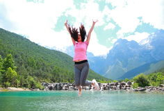 Healthy happy life, Asian Chinese jump by a lake. Asian Chinese woman yoga by a lake, Yulong snow capped mountains on the background, beautiful landscape Royalty Free Stock Images