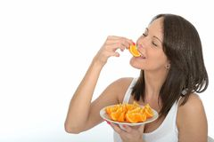 Healthy Happy Natural Young Woman Eating a Plate of Fresh Ripe Orange Segments. A DSLR royalty free image, a happy healthy natural young woman, holding a white Stock Image
