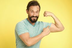 Healthy and happy. Sporty lifestyle and proper nutrition helps to keep youth and freshness even at mature age. Man with. Beard pointing at his muscular arm stock images