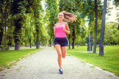 Healthy and happy woman running in urban park with headphones. And music Stock Photo
