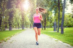Healthy and happy woman running in urban park. With headphones and music Royalty Free Stock Image