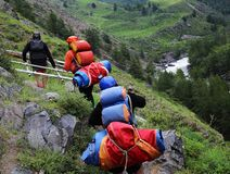 Healthy hardy  water-transport tourists go uphill with equipment for an alloy on rough river
