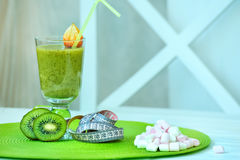 Healthy and harmful lifestyle. Smoothies with kiwi, a centimeter and a mountain of chocolates. Useful and harmful food is an opposition. Healthy and harmful Royalty Free Stock Photography