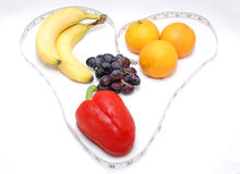 Healthy heart. Fruits and vegetables wrapped in a heart shaped tape measure against a white background Royalty Free Stock Photo