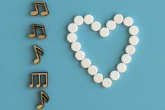 Healthy heart concept. The heart works like a note. Music notes and a heart on a blue background. stock photography