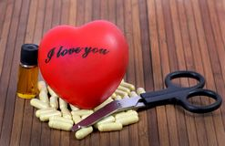 Healthy heart. Concept image showing supplement pills with red heart on wooden background Royalty Free Stock Photo
