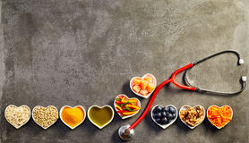 Healthy heart food concept. With a row of heart-shaped dishes with oats, salmon, turmeric, lentils, peppers, olive oil, acai, walnuts and carrot forming a Stock Image