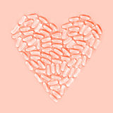Healthy heart made from pills, on pink background Stock Image