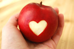 Healthy Heart Red Apple. Healthy red apple with a heart carved into it being held in a hand stock photo