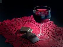 Healthy heart. Red wine and dark plain chocolate. Dark lighting. Stock Photos