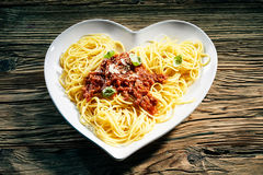 Healthy heart-shaped dish of Italian spaghetti. Topped with a spicy savory beef mince and tomato sauce, parmesan cheese and fresh basil on a rustic wood Royalty Free Stock Image