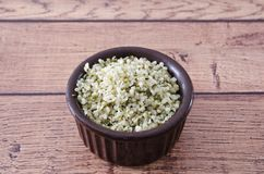 Healthy Hemp Hearts. In a brown bowl on wooden background.  Copy space and close up Stock Image