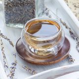 Healthy herbal lavender tea in oriental glass cup, square. Format stock image
