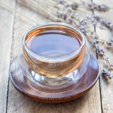 Healthy herbal lavender tea in oriental glass cup, square. Format stock photo