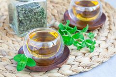 Healthy herbal mint tea in oriental glass cup with fresh peppermint and tea jar on background Royalty Free Stock Photos