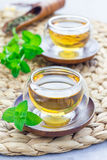 Healthy herbal mint tea in oriental glass cup with fresh peppermint and tea scoop on background Royalty Free Stock Photography