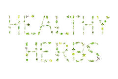 Healthy Herbs. Large selection of herb leaf sprigs, spelling the words healthy herbs, over white background Royalty Free Stock Image