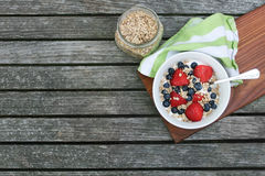 Healthy Homemade Breakfast Bowl with Berries. Granola in white bowl with greek yogurt and berries on wooden background, top view, type space, horizontal Stock Photo