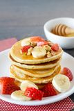 Healthy homemade breakfast with pancakes and fruits. Healthy homemade breakfast with pancakes, strawberry, bananas, nuts and honey Stock Images