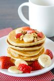 Healthy homemade breakfast with pancakes and fruits. Healthy homemade breakfast with pancakes, strawberry, bananas, nuts and honey Royalty Free Stock Photo