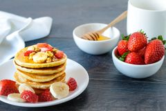 Healthy homemade breakfast with pancakes and fruits. Healthy homemade breakfast with pancakes, strawberry, bananas, nuts and honey Royalty Free Stock Photos